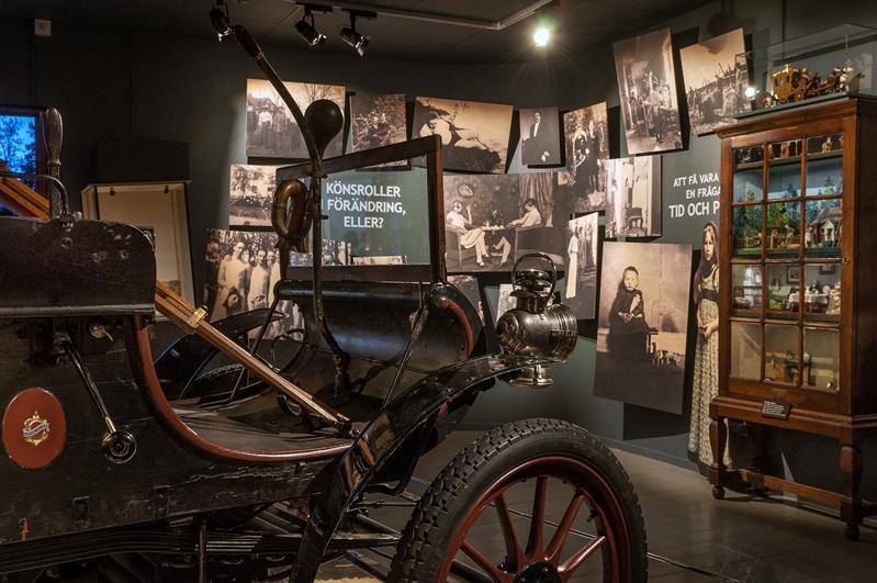 vy över utställning med fotografier på väggarna ett vitrinskåp och en gammal bil
