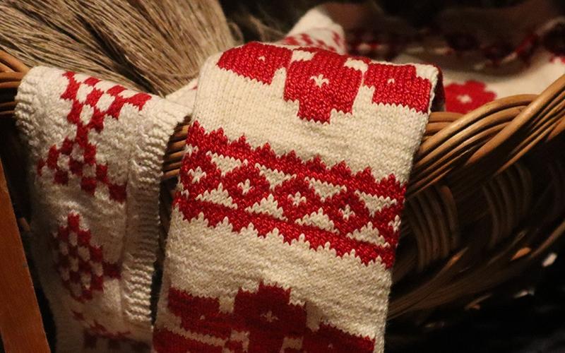 närbild på stickning med mönster i vitt och rött