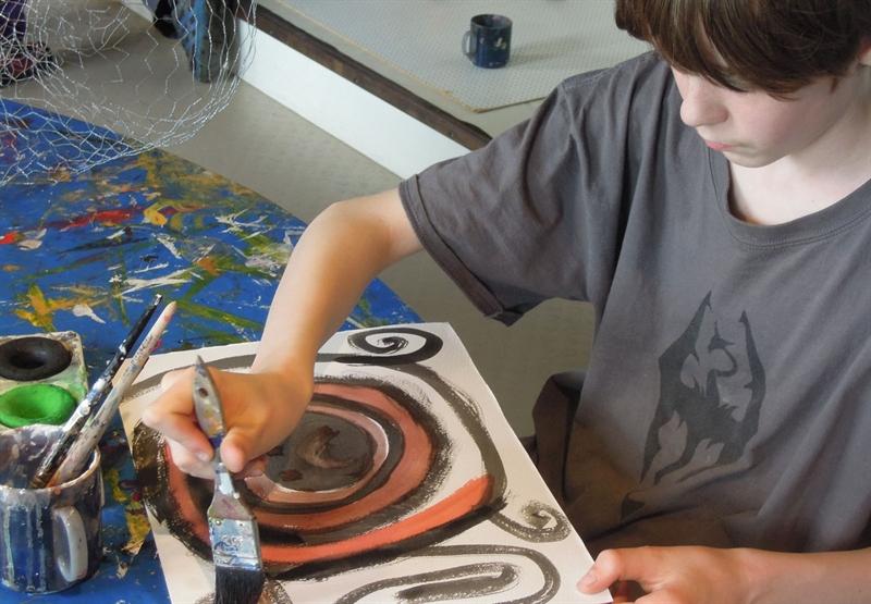 en pojke sitter och målar