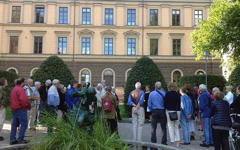 folksamling runt guide vid stor stenbyggnad