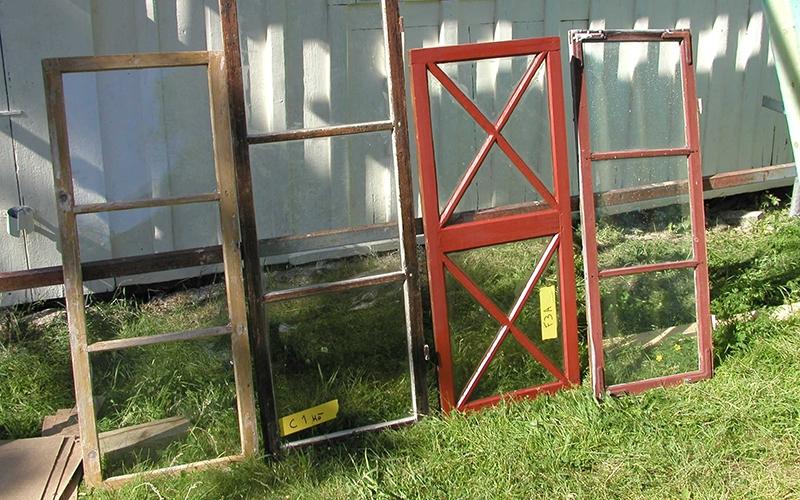äldre fönster i olika färger nedmonterade för restaurering