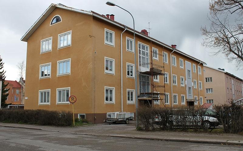 byggnadsställning vid gult, putsat bostadshus med vita fönster