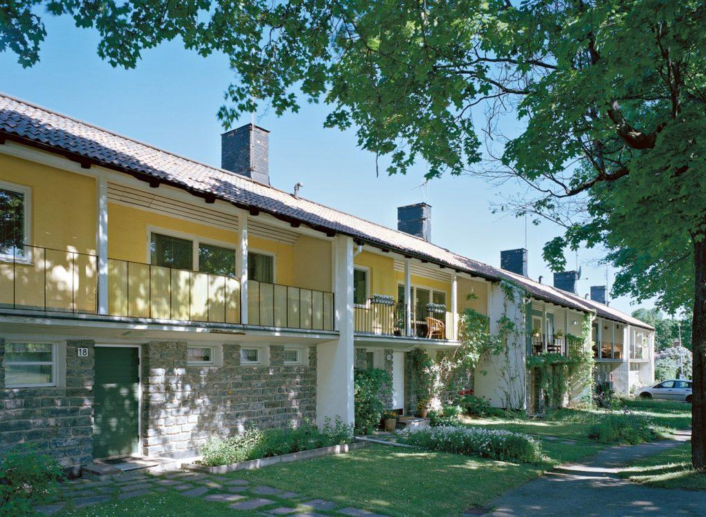 Gul arkitektritad radhuslänga med gröna dörrar