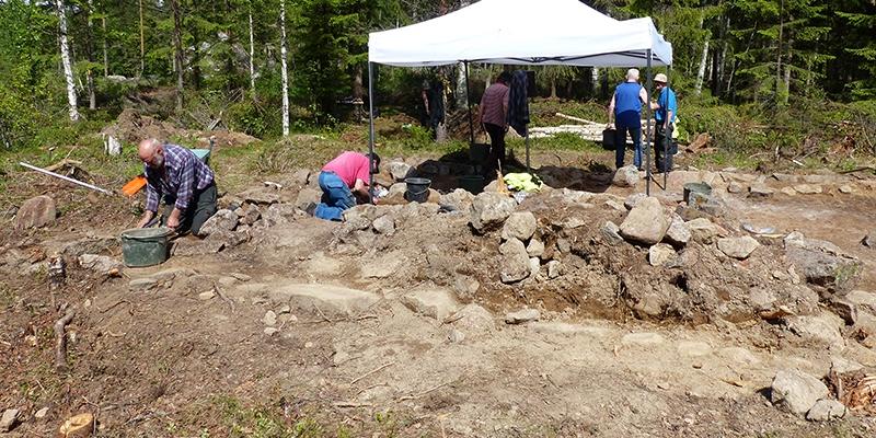 arkeologer arbetar vid uppmonterat skyddande tak