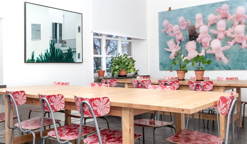 blommiga stolar runt träbord i grupprum med två tavlor och ett fönster
