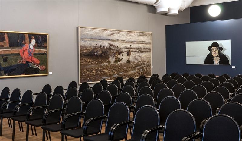 svarta stolar med högrygg uppradade i en hörsal. tre tavlor i bakgrunden