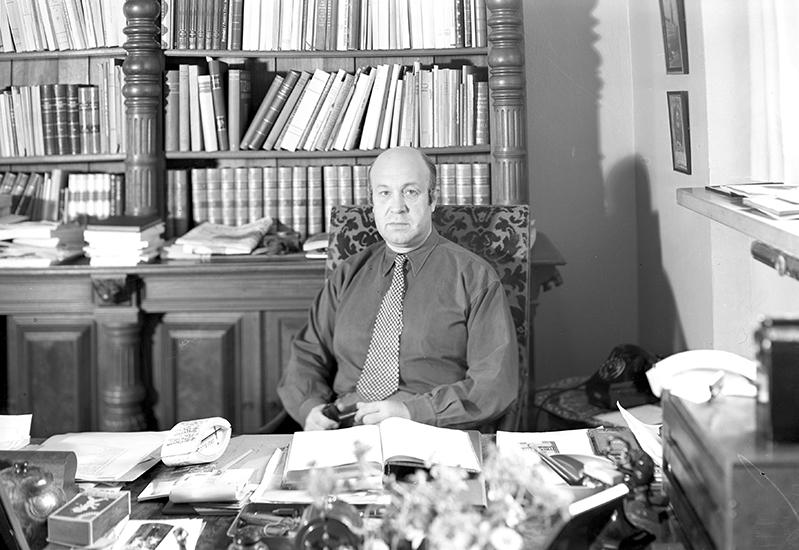 Humbla i mörk skjorta och rutig slips bakom rörigt skrivbord, bokhylla i bakgrunden