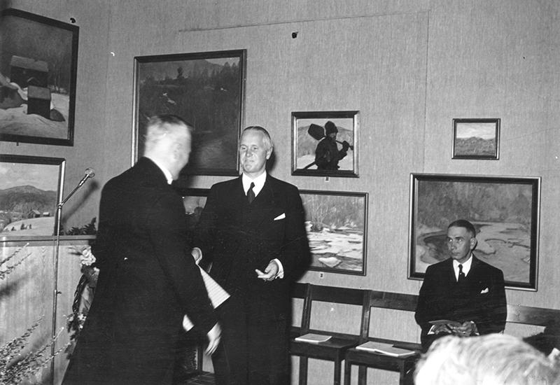 svart vit bild, två personer tar i hand, en tredje sitter ned, tavlor på väggarna.