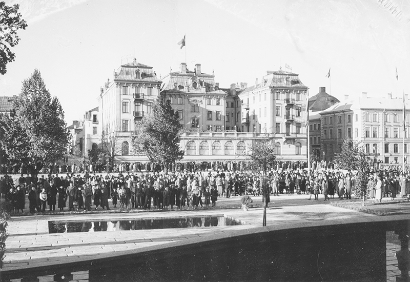 svart vit bild av publik som står samlade framför utsmyckad byggnad