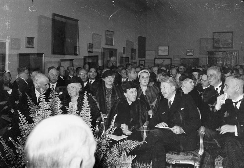 Svart vit bild, sittande publik i rader, välklädda herrar och damer i hattar.