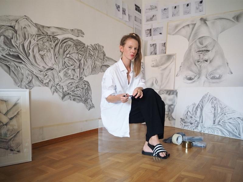 Josefin Lindskog i vit skjorta och svarta byxor i atelje med tavlor i bakgrunden