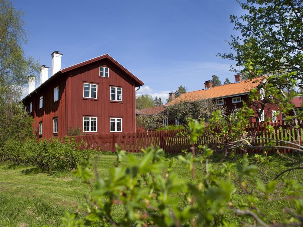 röd hälsingegård med rött staket i gönskande sommar och blå himmel