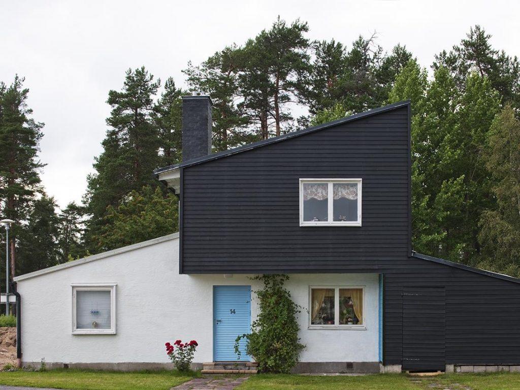 Arkitektritad villa. Vitputsad nedervåning, svart träpanel som övervåning och blå dörr.