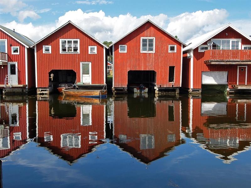 röda båthus på rad vid fiskeläge, blå himmel och spegelblankt vatten
