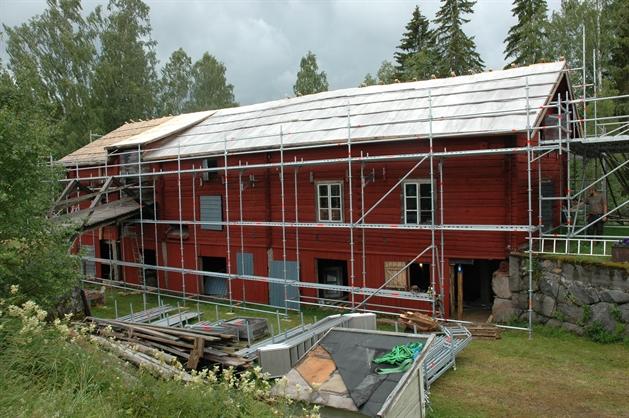 byggställningar utanför rödmålad kvarnbyggnad