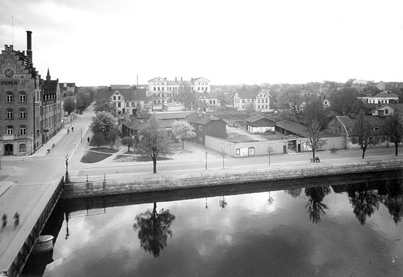 svart vit bild, låga byggnader, ljust plank, en bro med vatten i förgrunden