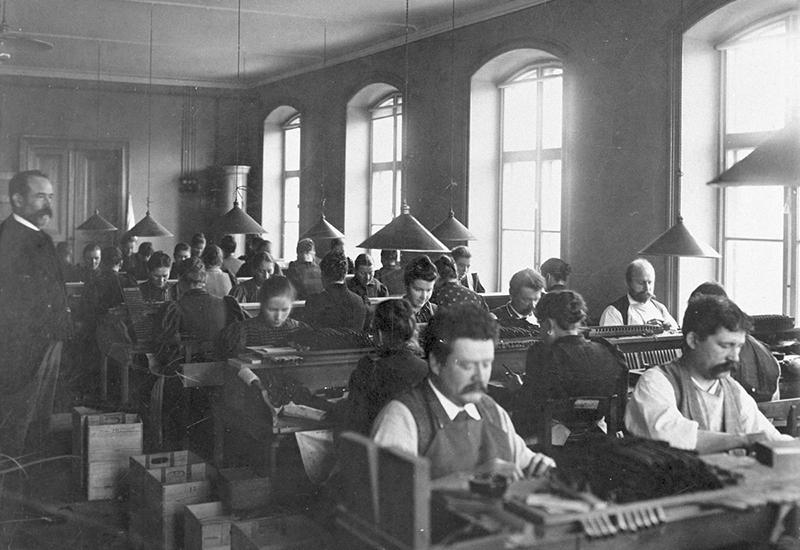 svart vit bild, fabriksmiljö, sittande arbetare i rader, kon-formade taklampor stora fönster