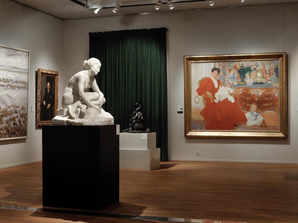 konstsal med skulpturer och tavlor