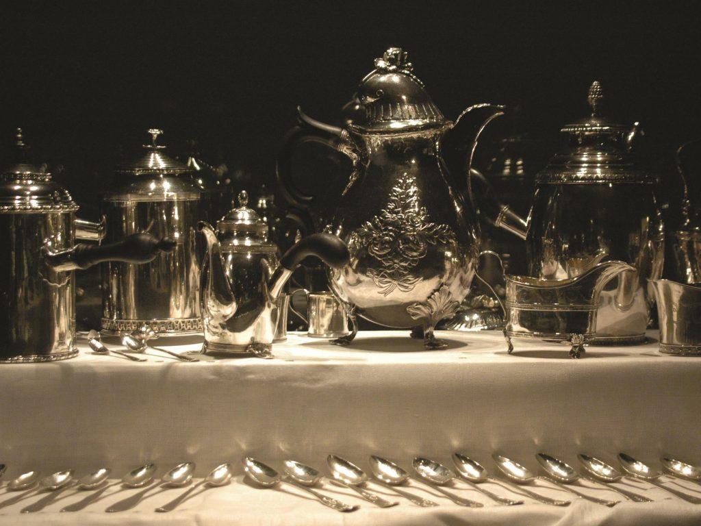 silverkannor och silverskedar uppradade på vid duk