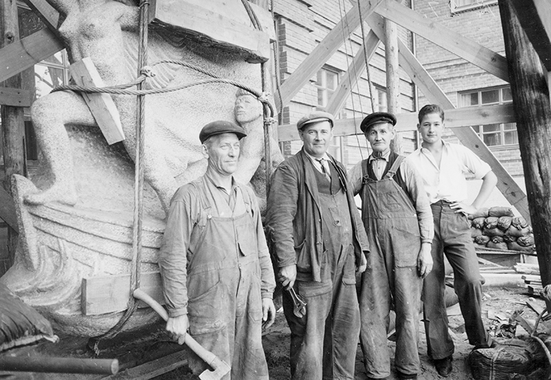 svart vit bild med fyra arbetare i keps och hängselbyxor framför stenrelief