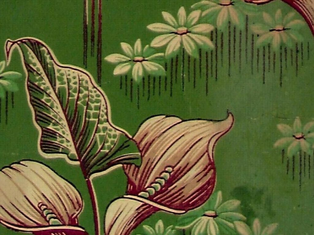närbild på grön tapet med mönster av blommor och blad