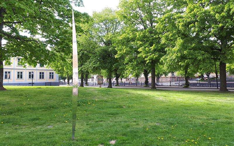 skulptur i metall som blänker bland grönskande träd och gräs