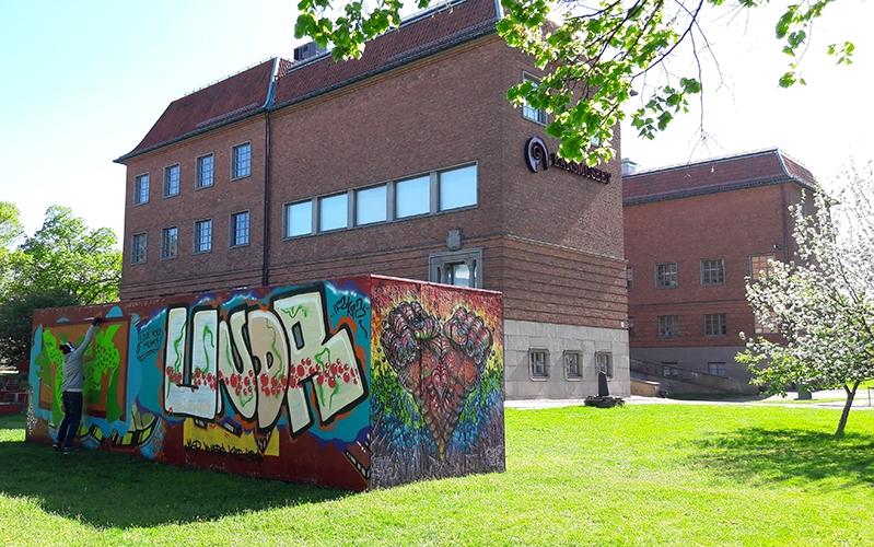 Grafittivägg och museets tegelbyggnad i solsken och grönskande gräs