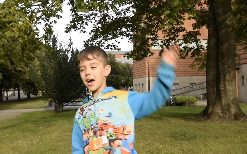 vinkande pojke i blå tröja framför museets byggnad