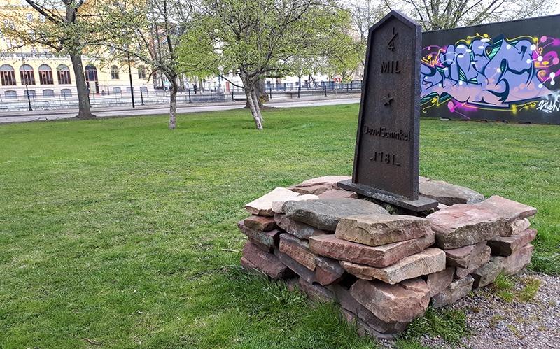 svart milstolpe i järn med stenar runt, grönt gräs och en grafittivägg i bakgrunden