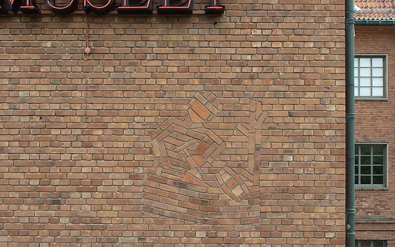 ett murat mönster i tegelfasad som bildar en man i en båt