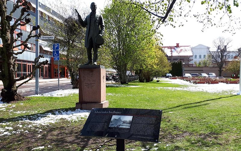 Staty skulptur på gräsmatta med smältande snöhögar