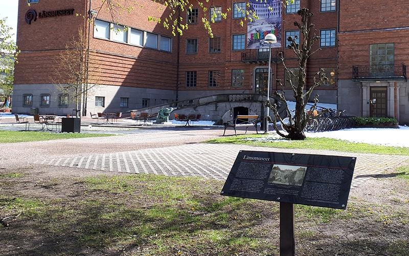 svart skylt på pelare som beskriver byggnaden i bakgrunden