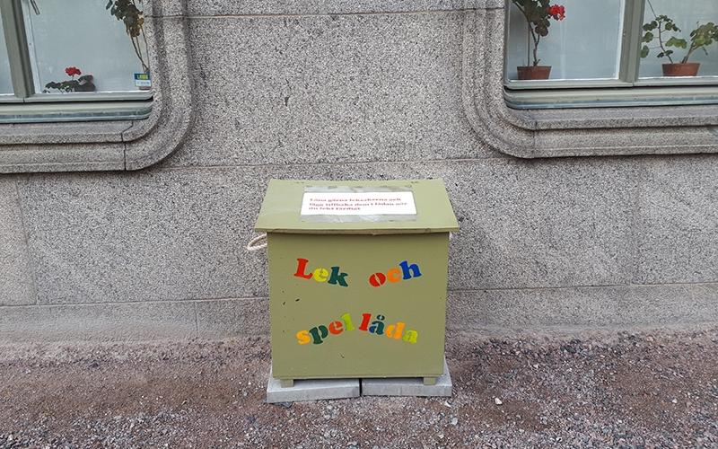 grön låda med lock och färglada bokstäver