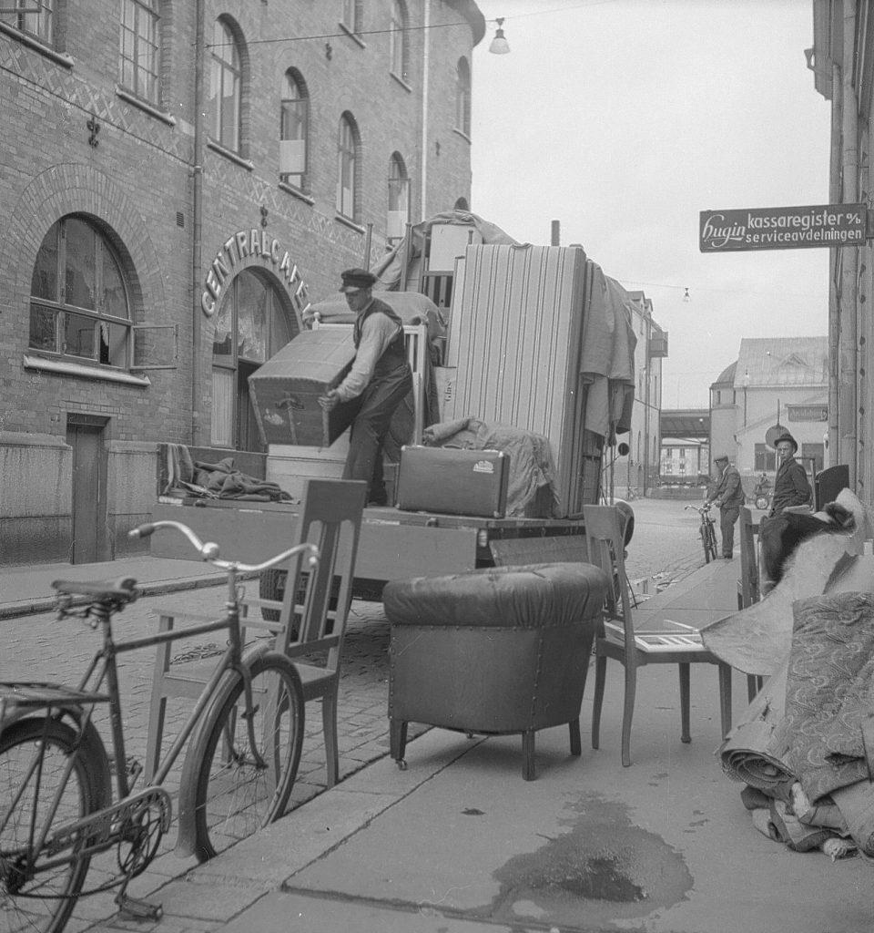 äldre svartvit bild. En man lyfter en låda på flyttlass och möbler står på trottoaren