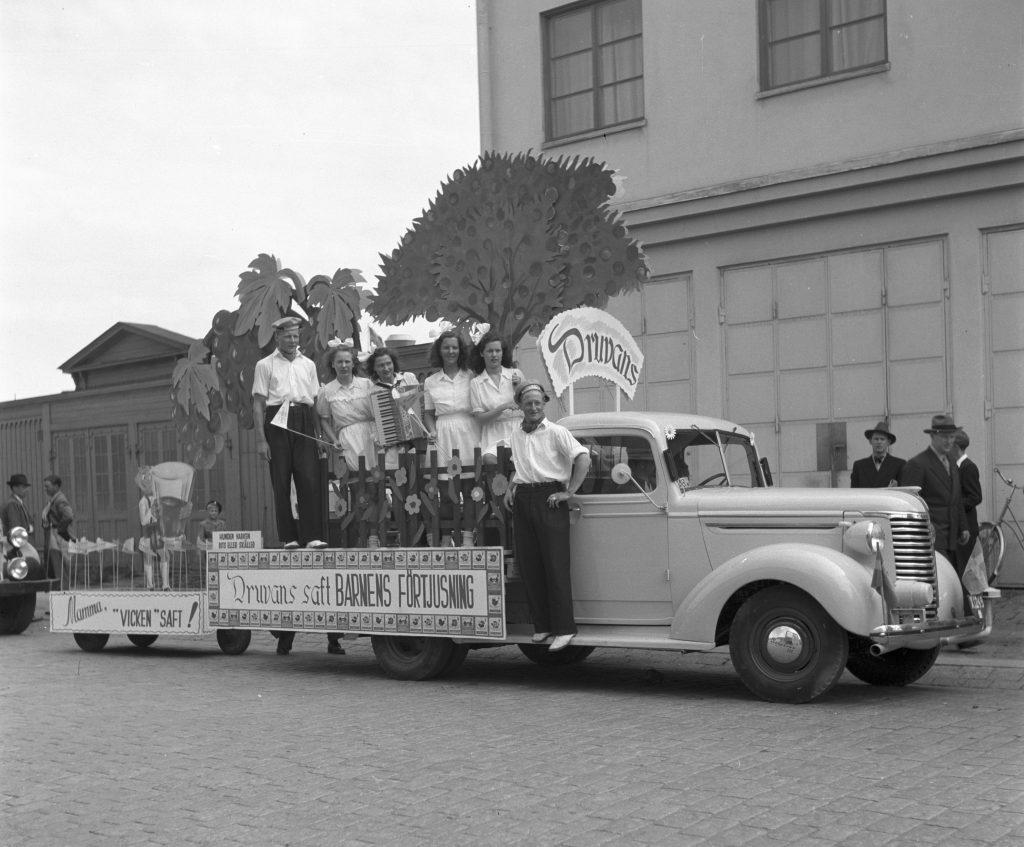 gammal lastbil dekorerad med skyltar och målade frukter och träd och personer stående på flaket
