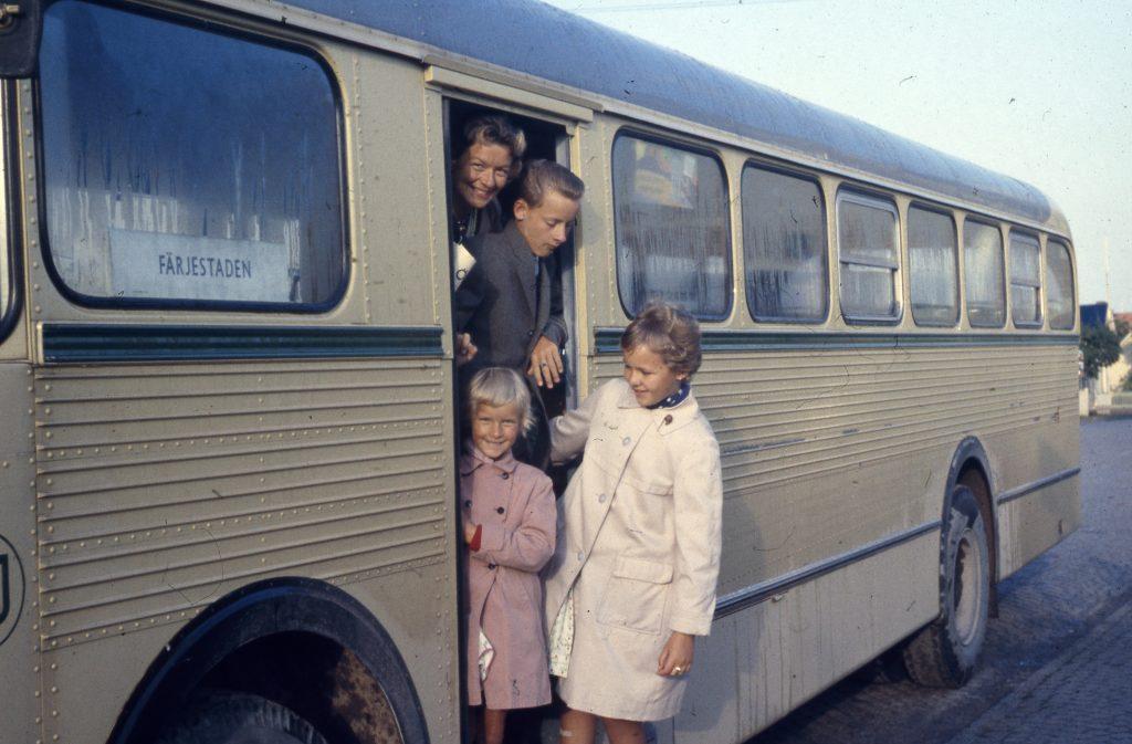 glad familj stiger ur beige buss med skylt som säger Färjestaden