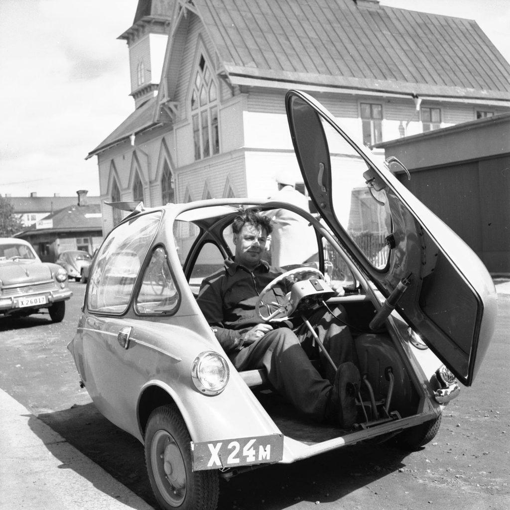 Man i parkerad trehjulig bil med öppnad dörr framtill