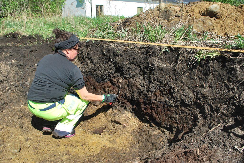kvinna i arbetsbyxor sitter i grop och gör arkeologisk undersökning