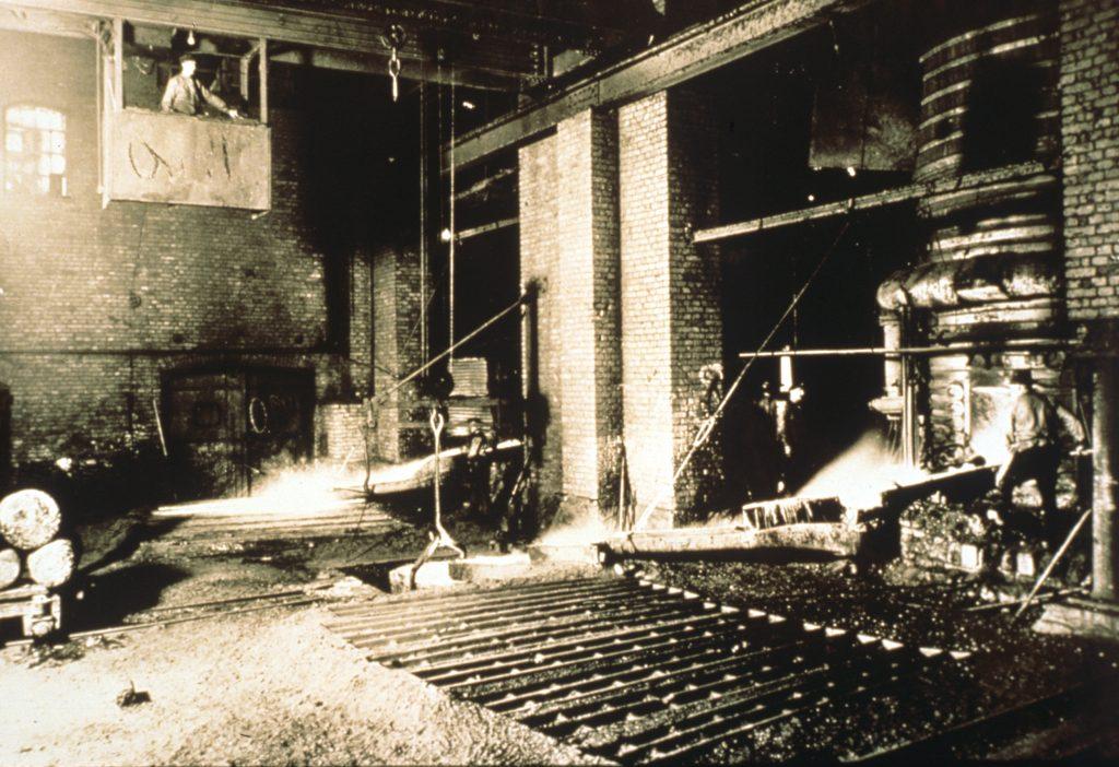 svartvit bild av bruksmiljö med järntillverkning