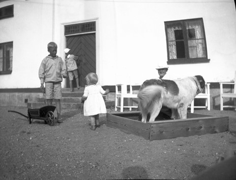 svartvit bild av barn och hund som leker i herrgårdsmijö