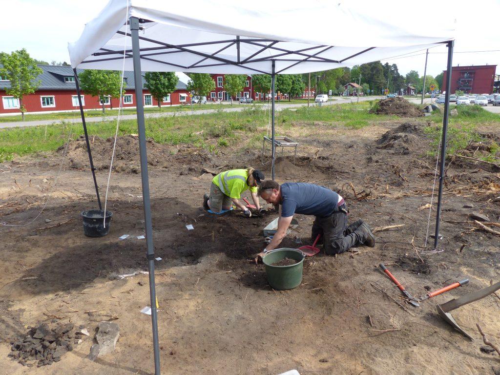 arkeologer gräver i marken under uppmonterat skyddande tak