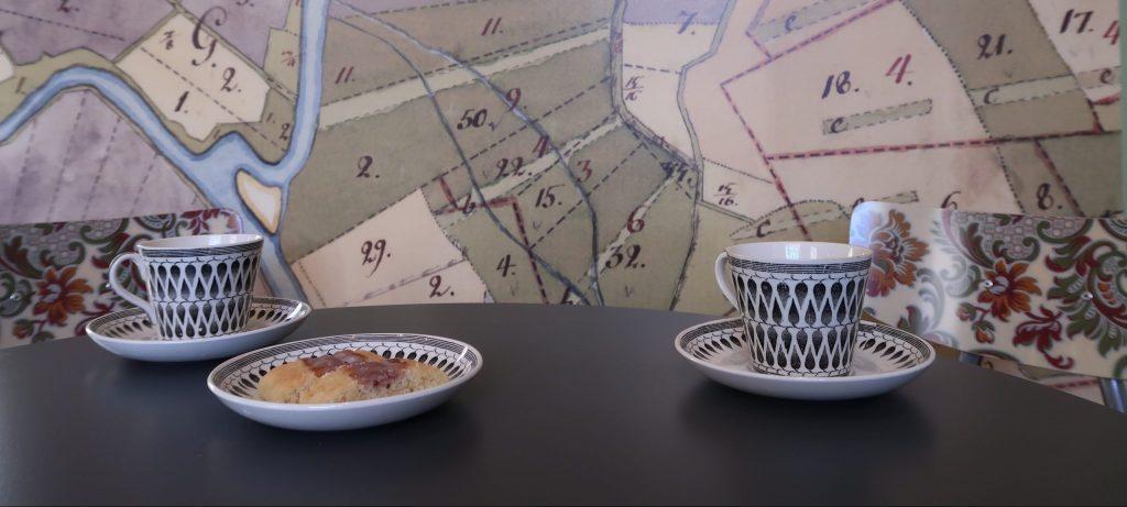 kartmönstrad tapet mönstrade kaffekoppar och syltkakor på svart bord