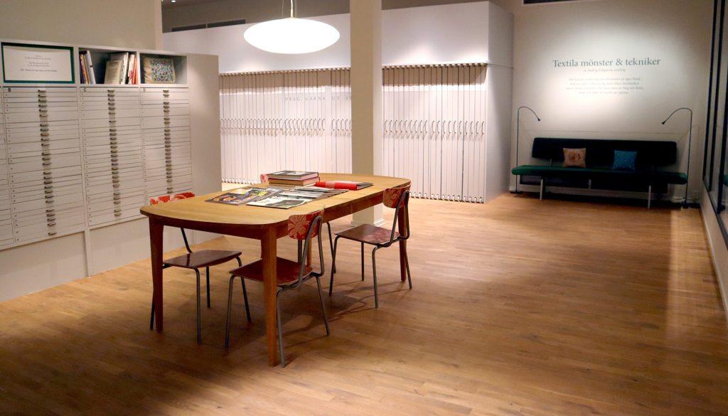 sal med arkivskåp bord och stolar tidningar och böcker