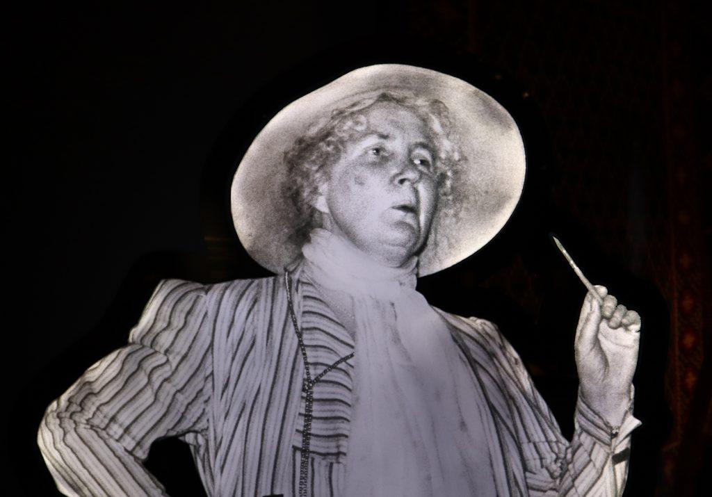 svartvit bild av kvinna i ljus hatt, sjal och randig dräkt