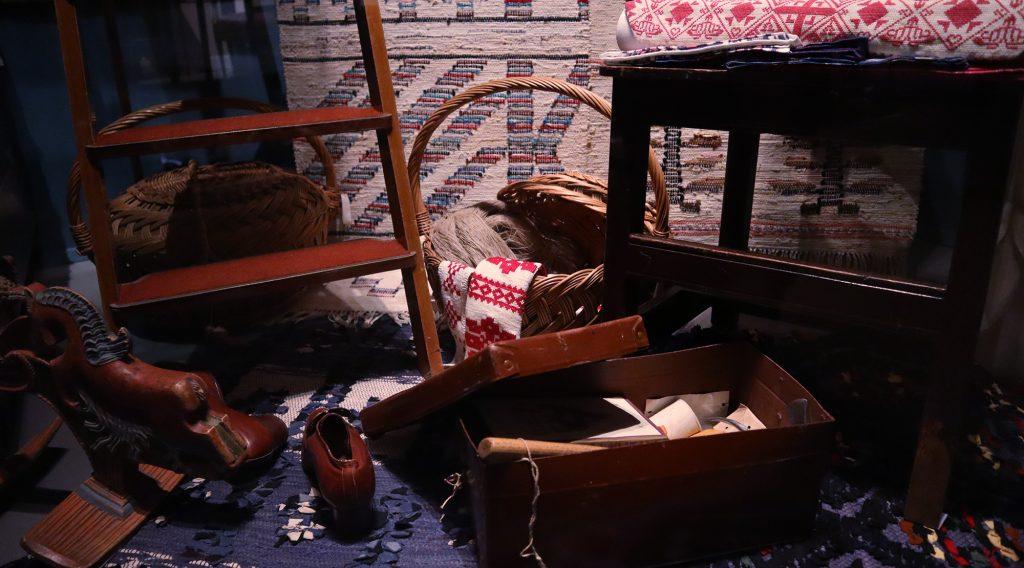 närbild på objekt i glasmonter, korg med textil, låda med verktyg trappstege