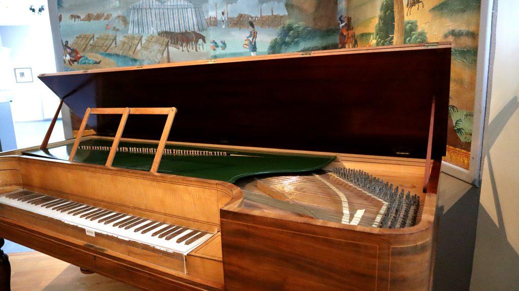 äldre flygel piano med gröna detaljer i brynässalen
