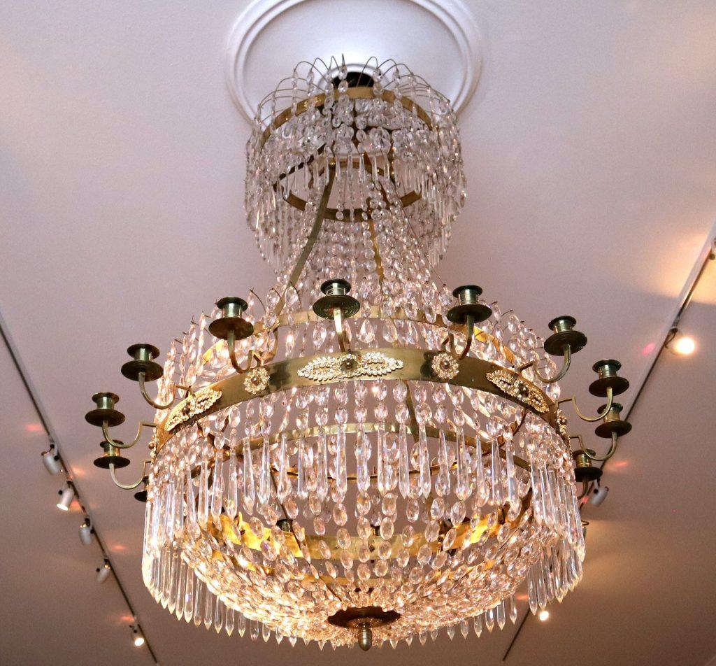 stor kristallkrona med prismor hängandes i brynässalens tak