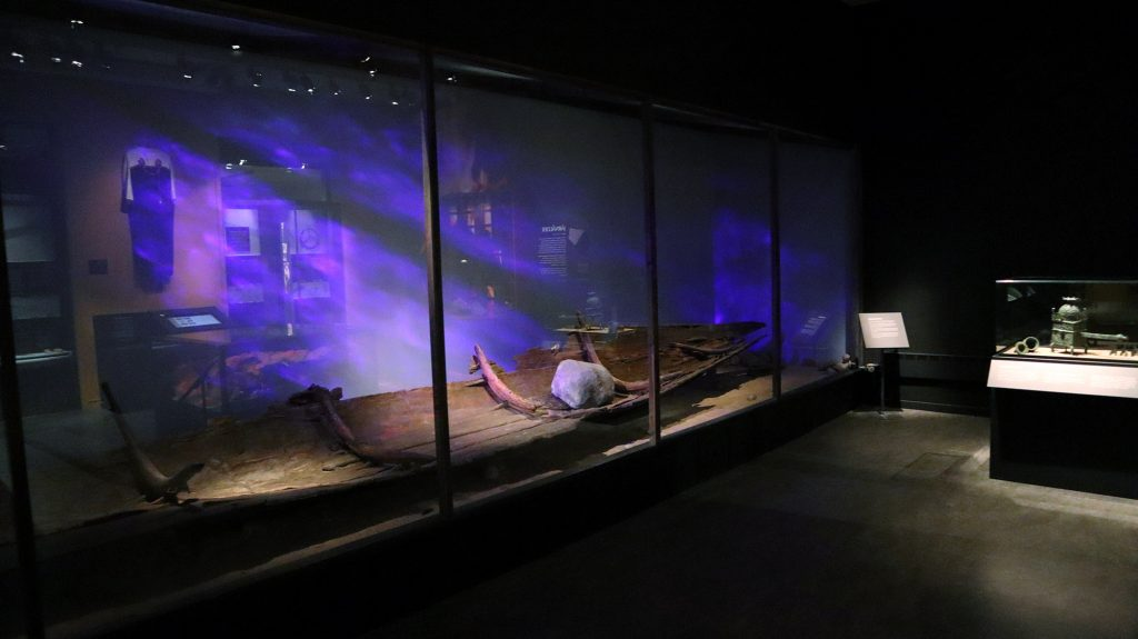 Stor glasmonter med en gammal stockbåt av trä