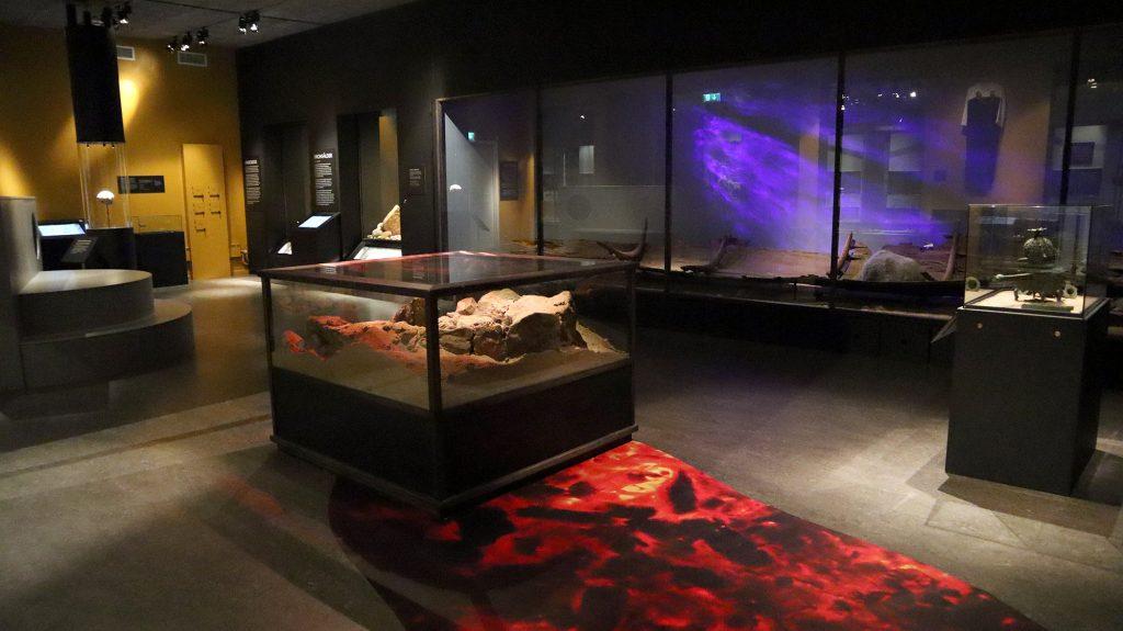vy över utställningssal med svarta väggar och glasmontrar med arkeologiska fynd