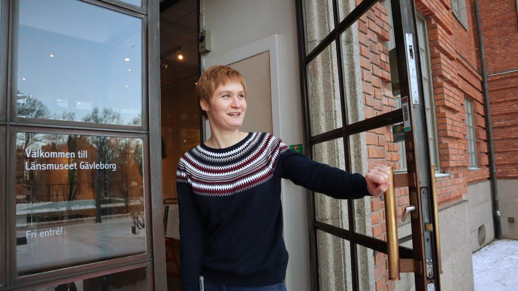 glad medarbetare håller upp glasdörr med mässingshandtag